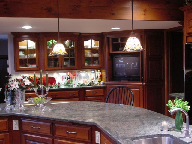 Custom cherry kitchen cabinets with glass doors in the Langhorne area of Lower Bucks County. Kitchen remodel. Our cabinets are set with LED lights and glass shelves. The island is custom on an angle for easy flow around the room with plenty of room for stools.